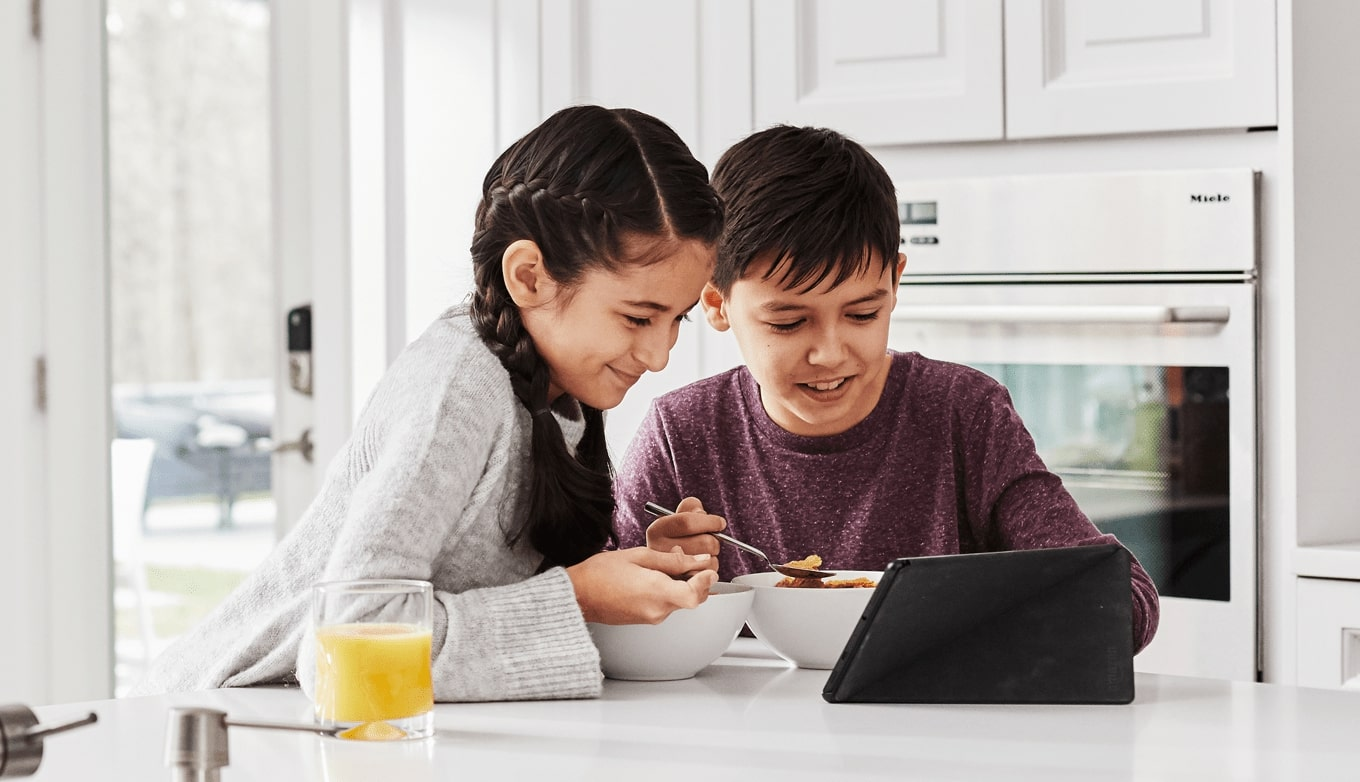 Kids in kitchen, eating cereal watching a tablet